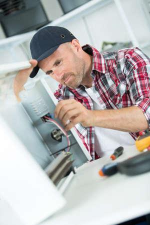 fixing: smily repairman fixing computer unit