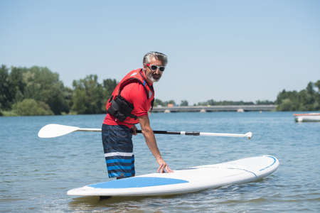 healthy men: man next to a stand-up paddle board on the lake Stock Photo