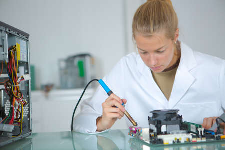 soldering: girl with a tester and a printed circuit board