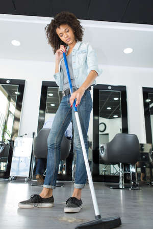 overtired: worker floor cleaning at a hairdressers Stock Photo