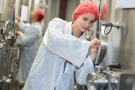 vats: woman inspecting wine vats inside winery Stock Photo