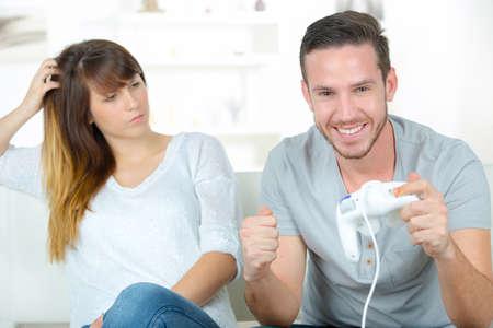 jugando videojuegos: mujer infeliz con su marido jugando videojuegos