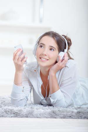 Lady lying on rug, listening to headphones