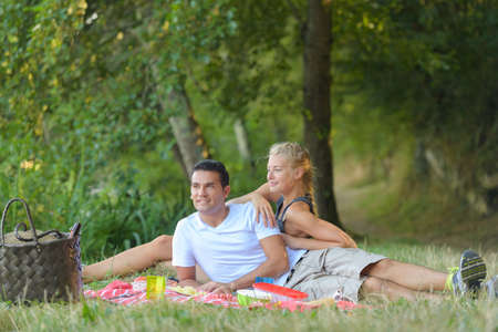 beautiful young couple having picnic in countryside Stock Photo