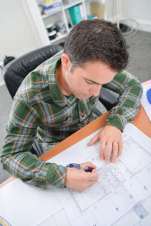 amend: Man working on scale drawings Stock Photo