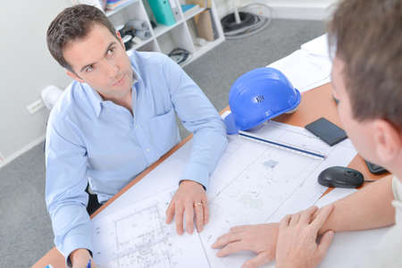 confer: Two men at desk looking at blueprints Stock Photo