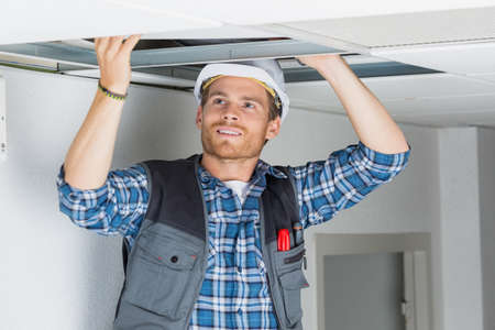 ceiling slab: worker installing ceiling slab in a house Stock Photo