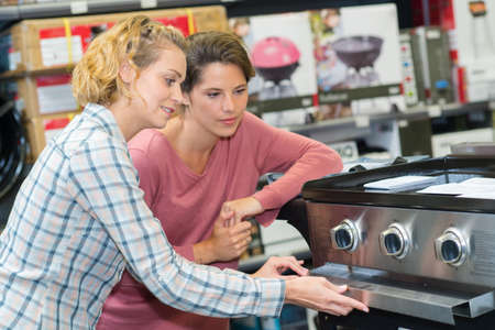 smily woman buying an oven in hypermarket