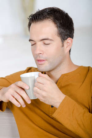 middle-aged man savouring the aroma of a cup of coffee