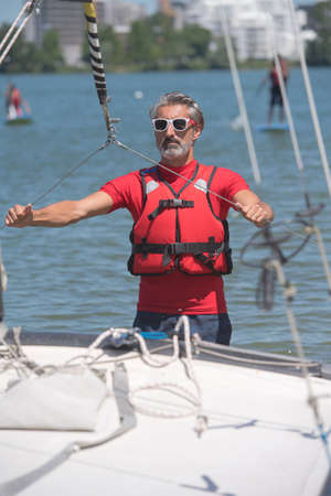 portrait of mature sportsman near catamaran
