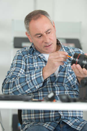 man cleaning lens by brush Stock Photo