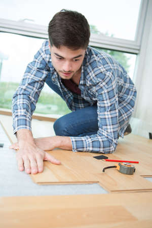 tongue and groove: Man fitting laminate flooring