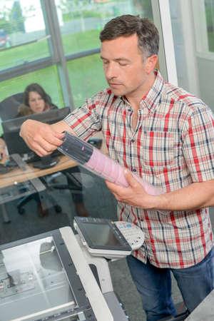 desk clerk: man replacing toner