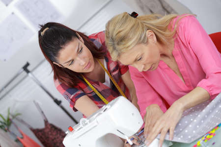 woman clothes: fashion designer using sewing machine training an apprentice
