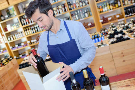 seller wearing apron preparing box with bottles in wine store Stock Photo