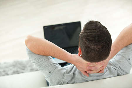 looker: young man lying on sofa watching video on laptop