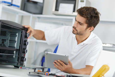 attractive repairman concentrated at work Stock Photo