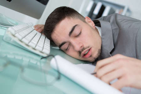 tried: man tried from working and sleeping on working desk