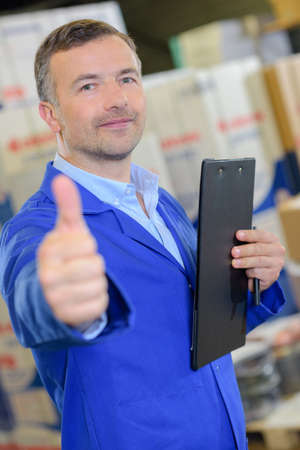 Man with clipboard making thumbs up Stock Photo