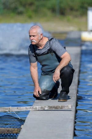 safty: fisherman with rubber boots working at fish farm