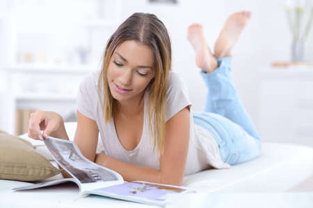 smiling woman lying on couch and reading magazine at home Stock Photo