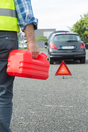 gas can: senior aged man holding gas can to refill his car