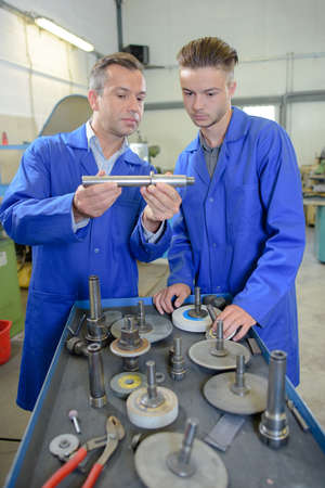 assessing: Engineers assessing parts in workshop