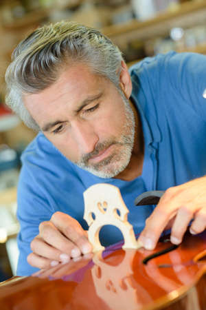 attaching: luthier attaching the bridge