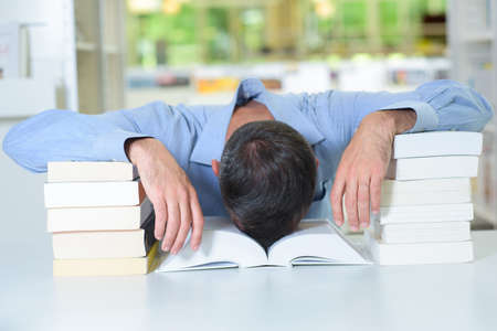 slumped: Man with head slumped in a book