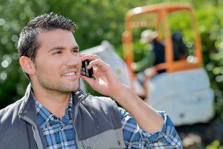 obrero: trabajador joven y sonriente en el teléfono Foto de archivo