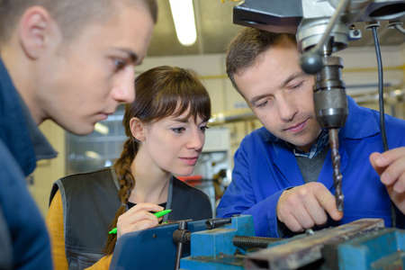 apprentices working on the machine - metal processing Stock Photo
