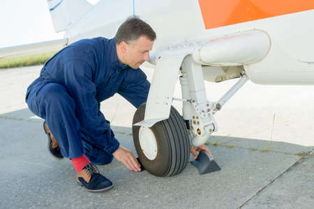 undercarriage: worker checking undercarriage of plane Stock Photo
