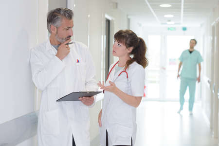 health professional: Medical workers in discussion in hospital corridor Stock Photo