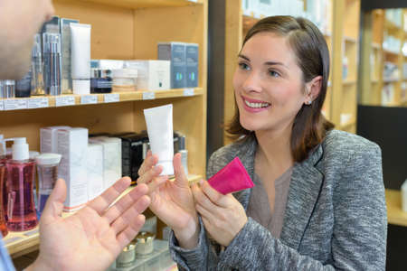 Saleswoman showing two beauty products to customer