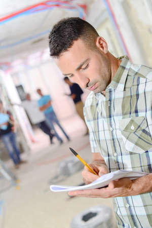 Man making notes, gathering at a construction site Stock Photo