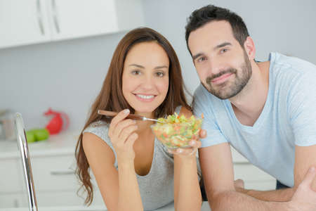 eating salad: Couple sharing a salad in the kitchen
