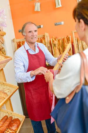 siervo: Panadero barra de pan que sirve Foto de archivo