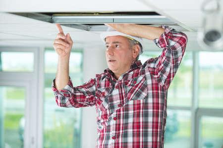 man repairing collapsed ceiling Standard-Bild
