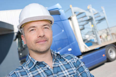 chofer: Retrato del hombre en el sombrero duro delante del camión