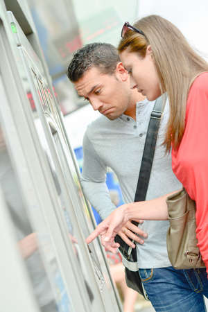 complicated journey: Couple using ticket machine, looking confused Stock Photo