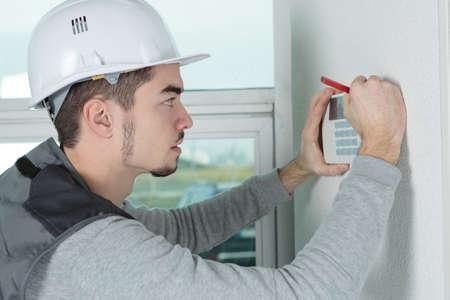 worker installing alarm system in office Standard-Bild