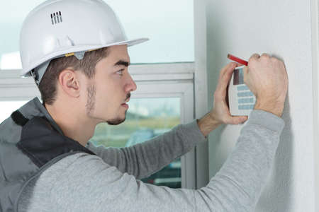 worker installing alarm system in office Stock Photo