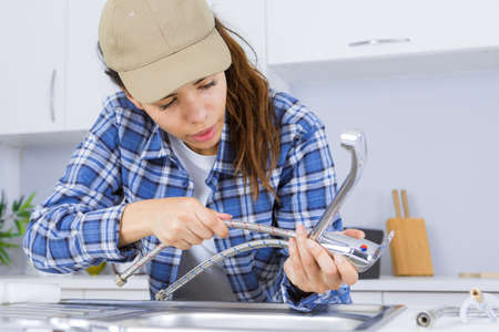 woman plumber fixing a sink