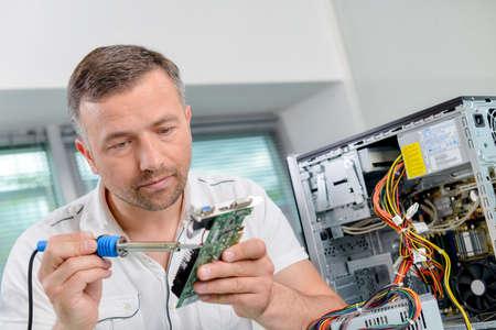 brazing: Man soldering computer component