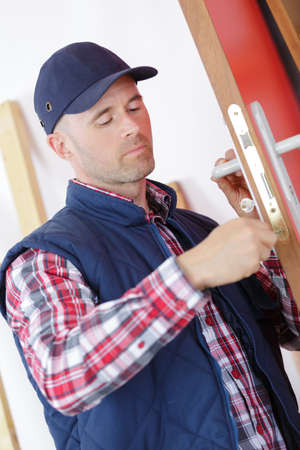 deadbolt: carpenter at lock installation into door