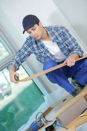 young technician installing floor at construction site Stock Photo