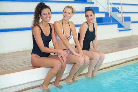 sexy füsse: Drei Frauen saßen am Rand des Swimming-Pool