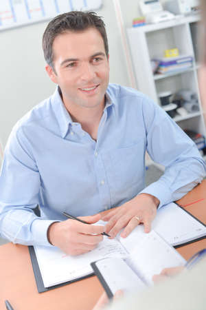 availability: Men at desk scheduling with their diaries Stock Photo