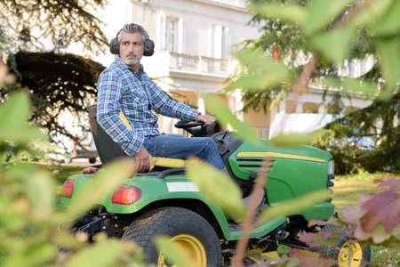 Hombre que usa el tractor cortacésped