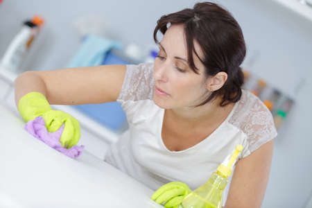 table surface: housewife cleaning surface of the table with disinfectant
